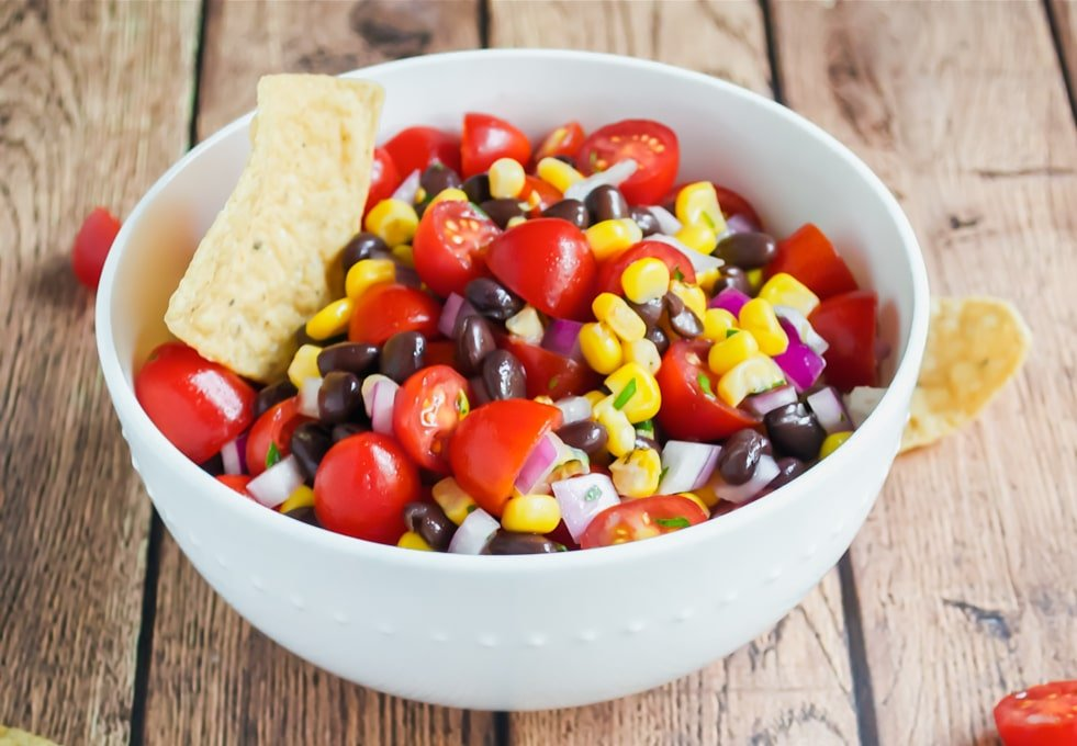 A white bowl full of cherry tomato, black bean, corn salsa with a tortilla chip in it.