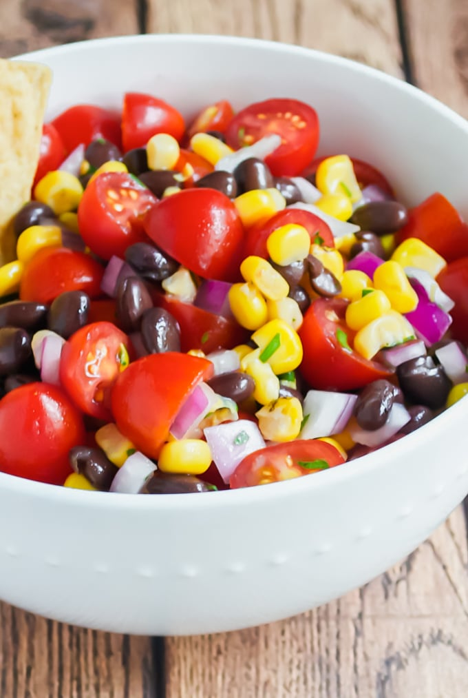 A closeup of a bowl with cherry tomato, corn, black bean salsa with red onions in it.