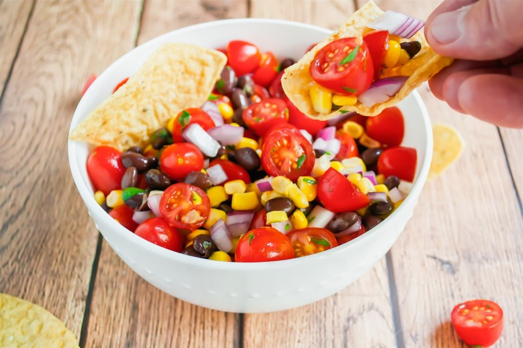A hand holding a tortilla chip with black bean, cherry tomato, corn salsa in it.
