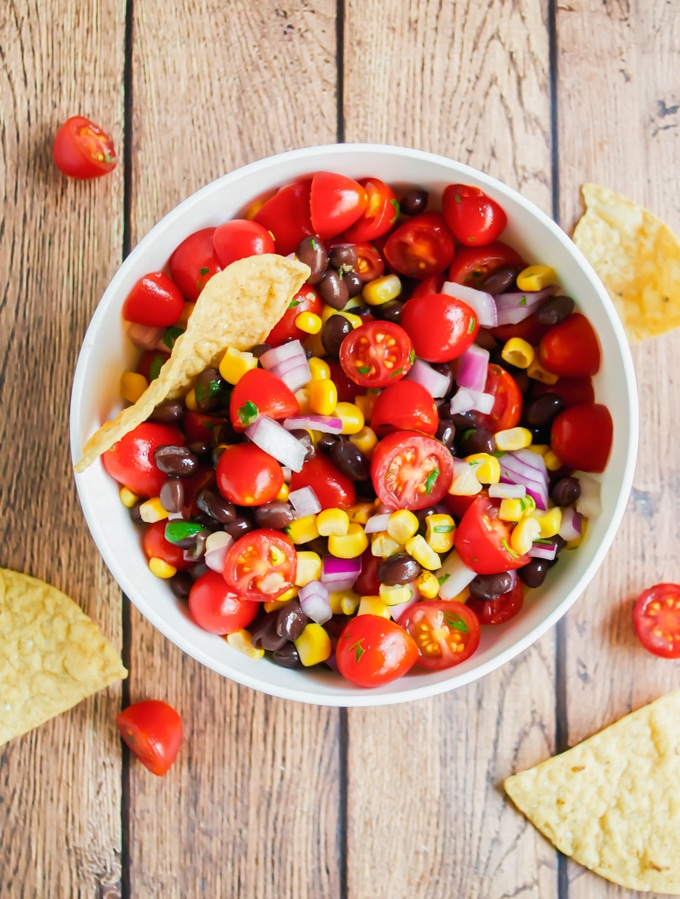 A bowl of cherry tomato, corn, black bean salsa with a tortilla chip in it.