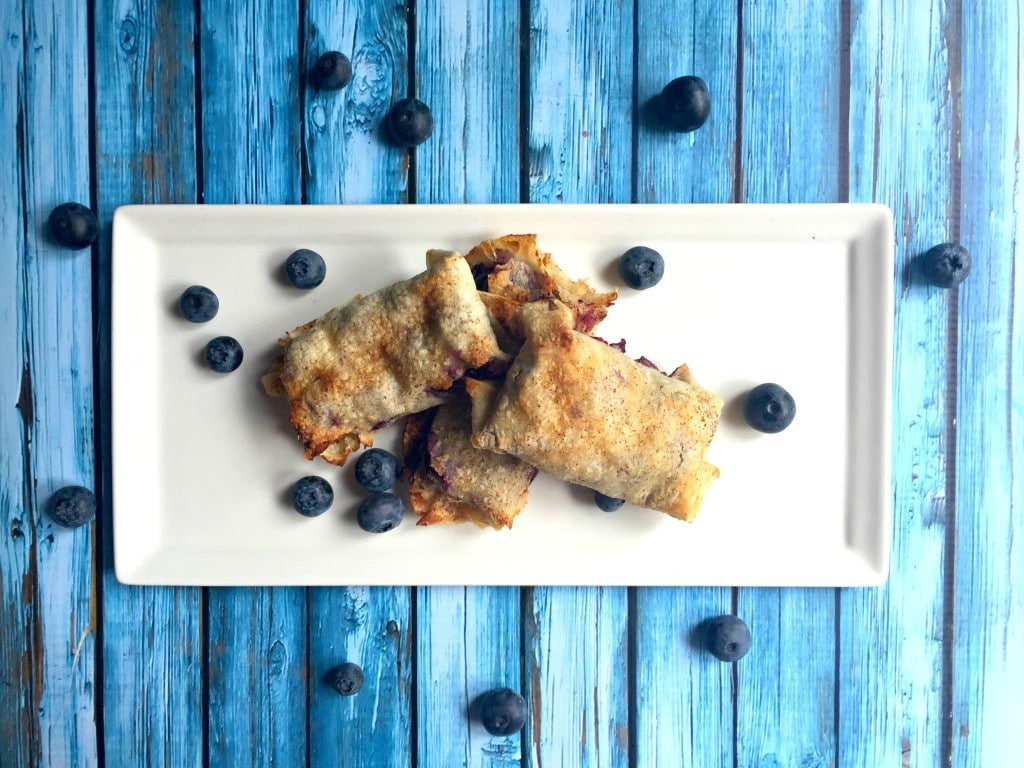 An overhead view of three blueberry tortilla pockets on a white platter with fresh blueberries.