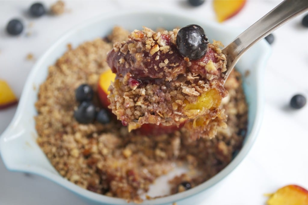 A spoonful of blueberry peach crisp being held over a casserole dish.