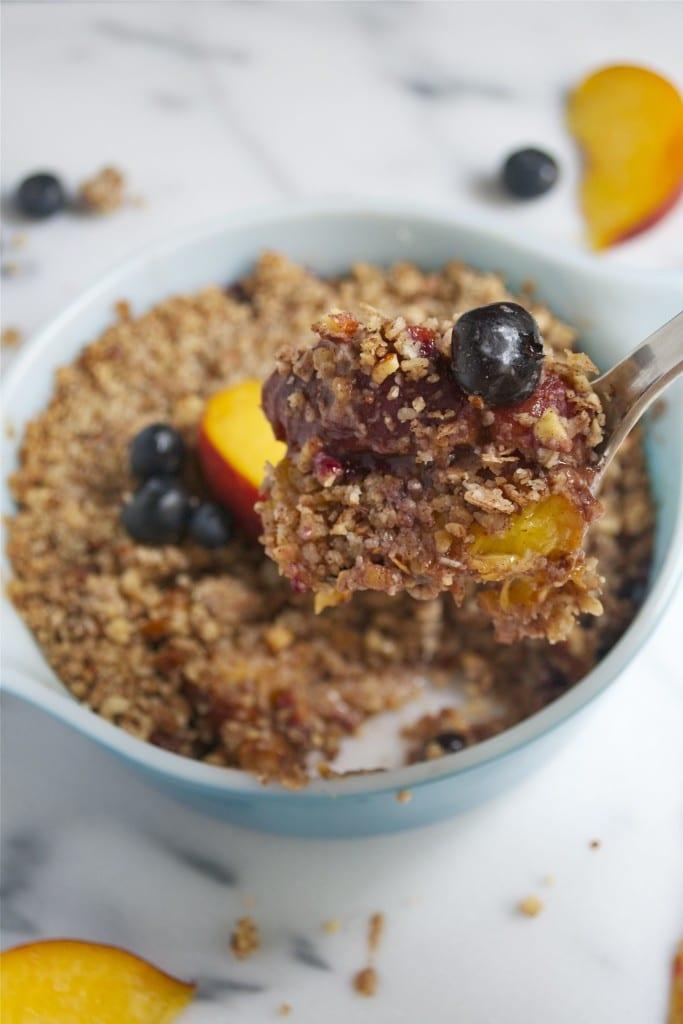 A spoon of blueberry peach crisp over a small casserole dish of crisp.