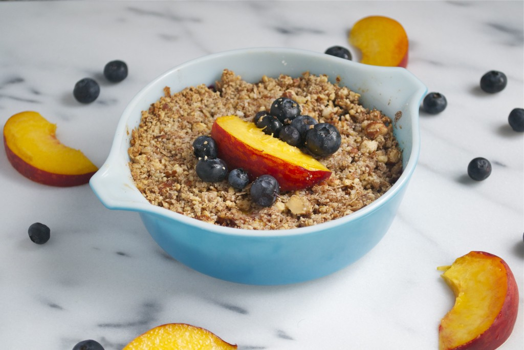 A small casserole dish of blueberry peach crisp with fresh peaches and blueberries on top.