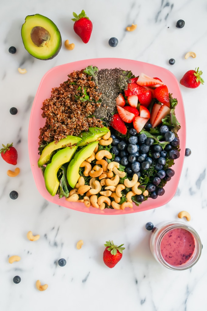 A pink serving bowl with quinoa, chia seeds, strawberries, blueberries, cashews, and avocado on a bed of lettuce.