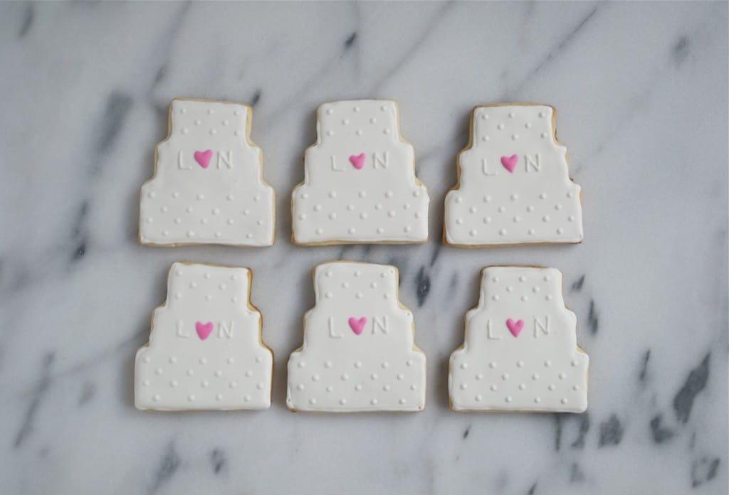 Six wedding cake sugar cookies decorated with royal icing on a marble table.