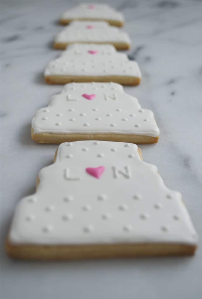 A row of wedding cake sugar cookies decorated with royal icing on a marble table.