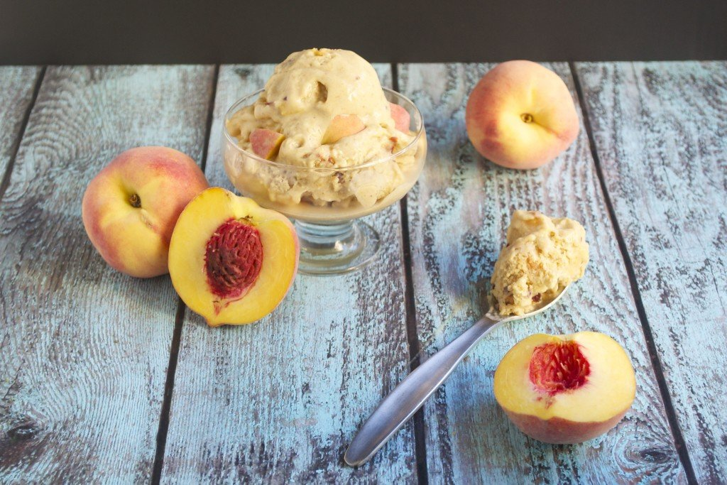A dish with vegan peach ice cream with fresh peaches in front of it.