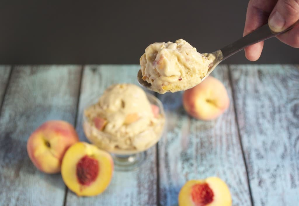A spoonful of vegan peach ice cream in front of a bowl of ice cream and fresh peaches.
