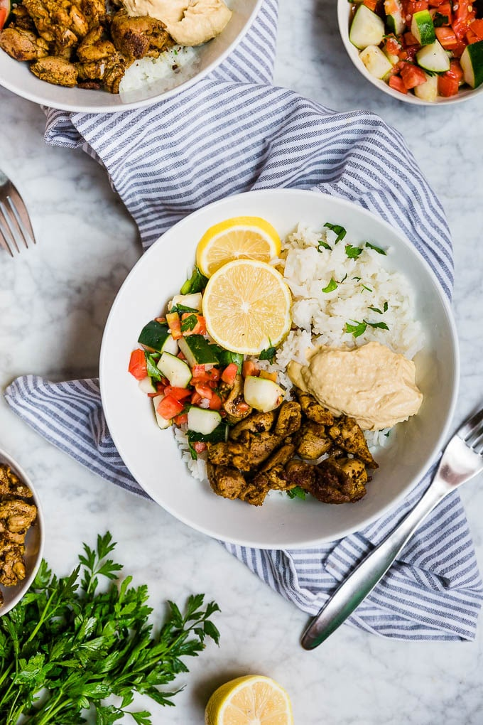 Easy meal prep mediterranean chicken bowls with rice, hummus and tomato cucumber salad.