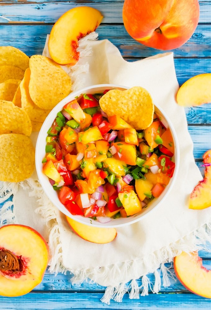 An aerial view of peach tomato salsa with tortilla chips and fresh peaches on the side.
