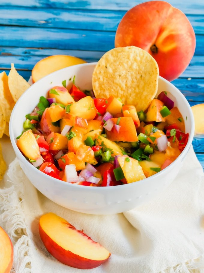 A bowl of peach tomato salsa with a tortilla chip in it and fresh peaches on the table.