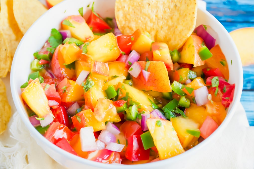 A bowl of peach tomato salsa with a tortilla chip in it.