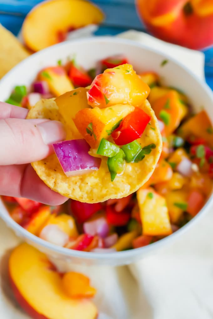 A hand holding a tortilla chip topped with peach tomato salsa over a bowl of salsa.