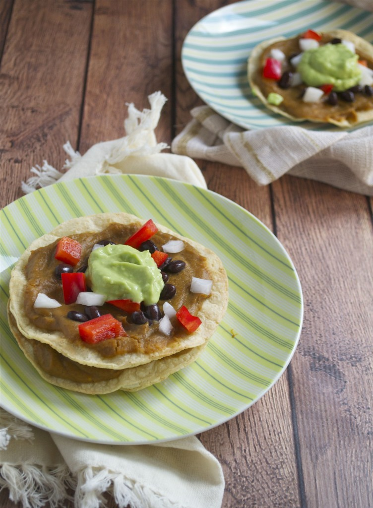 A plate of sweet potato tostadas topped with avocado cream, red onions, black beans and red bell peppers.