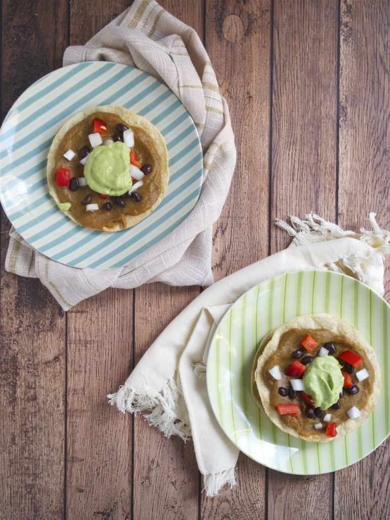 An overhread view of two plates with sweet potato black bean tostadas on them topped with avocado cream, red bell pepper, and onions.