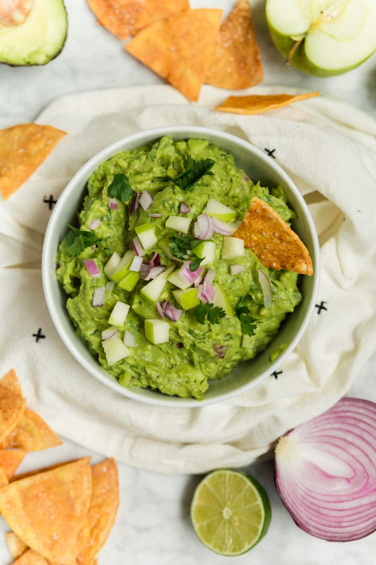 A bowl of green apple guacamole with baked tortilla chips, red onion, and limes.