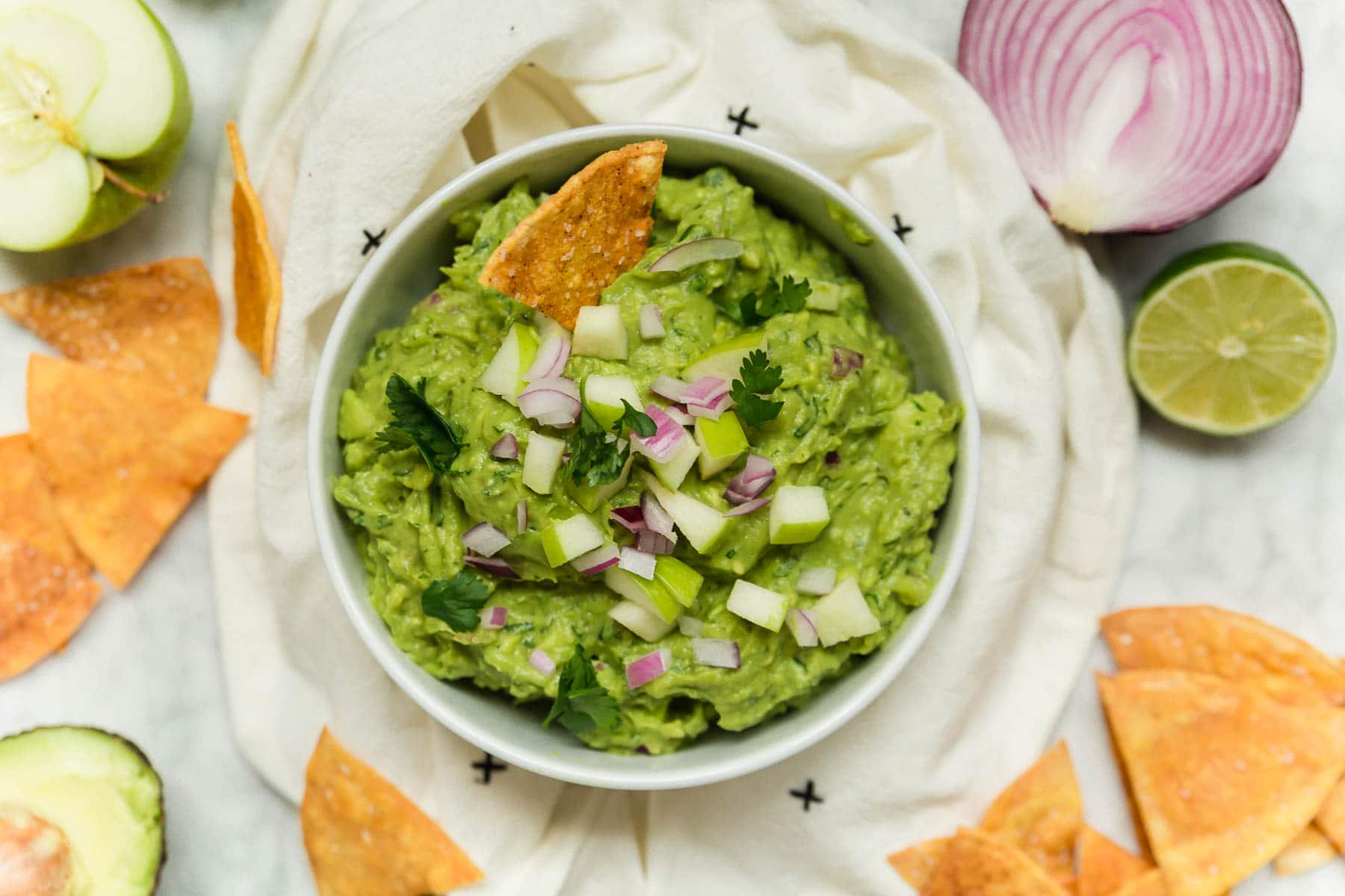 A bowl of apple guacamole with red onion, tortilla chips and lime.