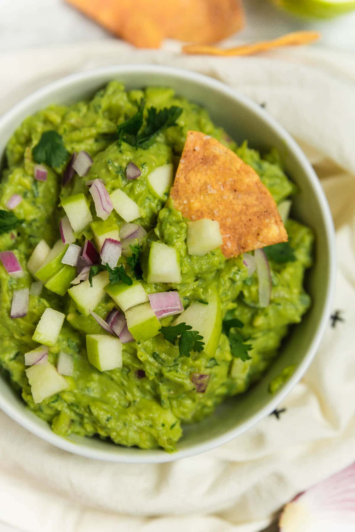 A bowl of guacamole with apple, red onion, cilantro and lime with a tortilla chip.