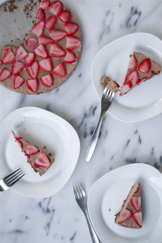 Plates of slices of vegan chocolate strawberry cheesecake with the full cheesecake on the side.