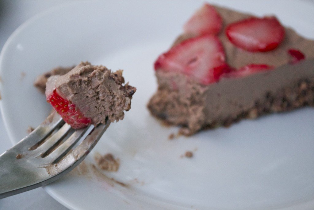 A slice of vegan chocolate strawberry cheesecake on a plate with a fork digging into the cheesecake.