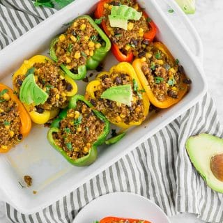 A baking dish with stuffed peppers filled with quinoa and beef and topped with avocado.