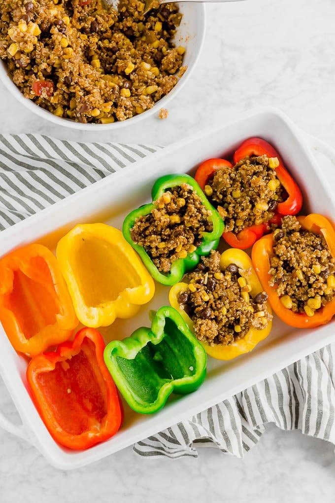 A baking dish filled with bell peppers of different colors being stuffed with a beef and quinoa mixture.