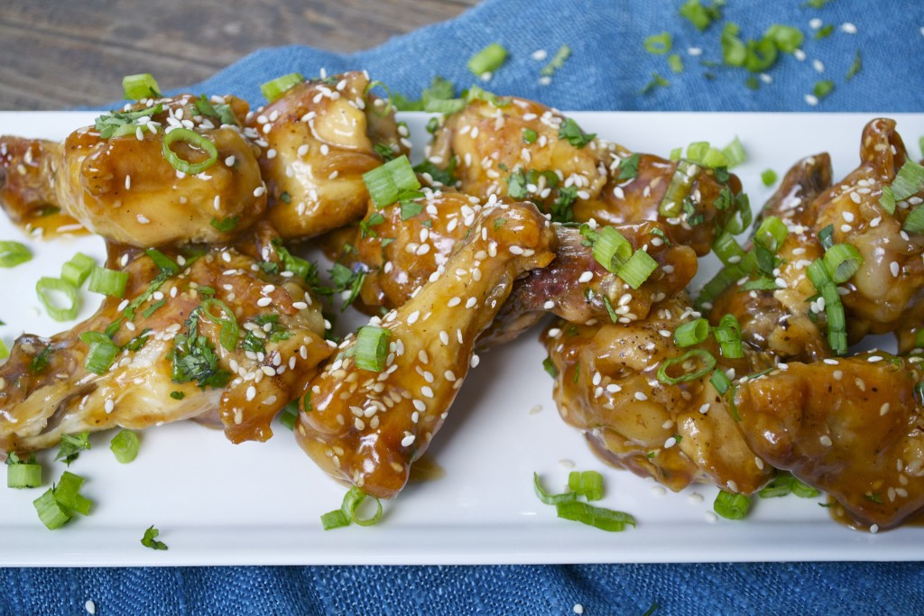 A platter of teriyaki chien wings topped with green onions and sesame seeds.