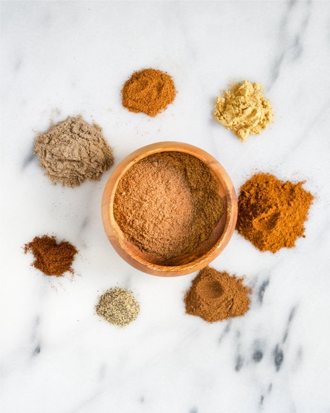 A small bowl of chai spice mix surrounded by individual spices used to make it.