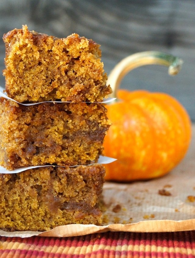 A stack of three pieces of pumpkin caramel coffee cake in front of a pumpkin.