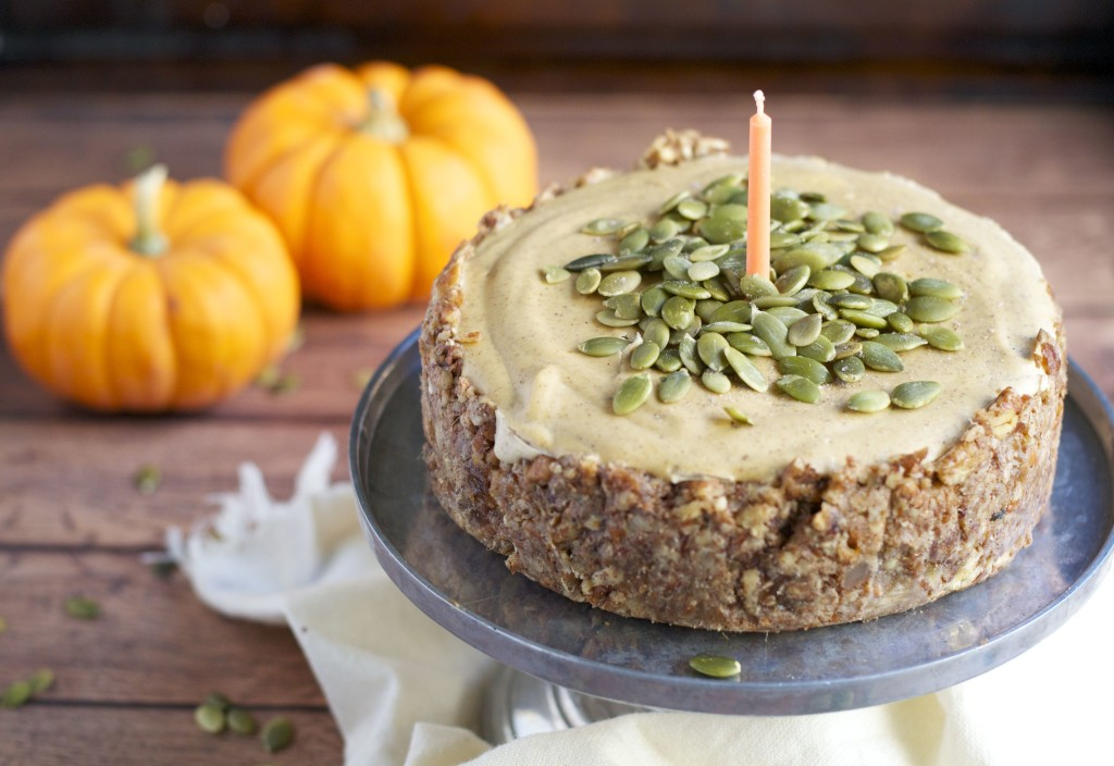A vegan pumpkin cheesecake topped with pumpkin seeds on a cake stand with mini pumpkins in the background.