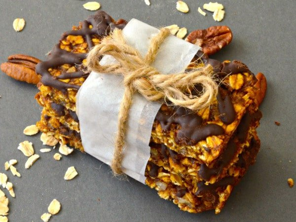 A stack of pumpkin granola bars with chocolate drizzle wrapped in parchment paper and twine.