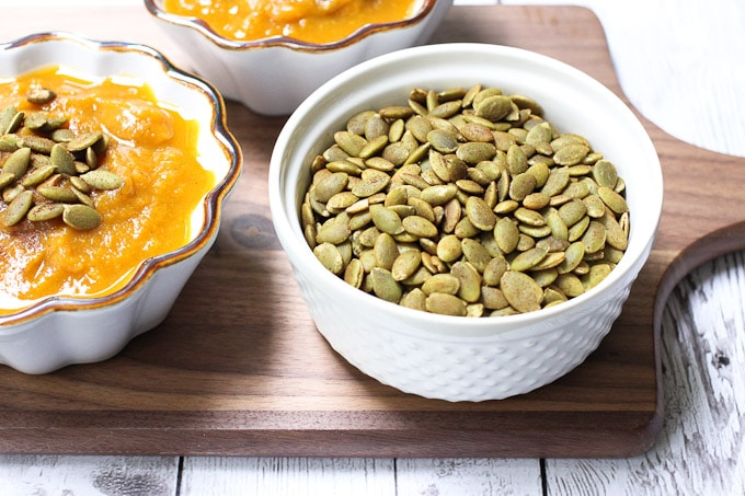 A bowl of pumpkin soup with a side of pumpkin seeds in another bowl.
