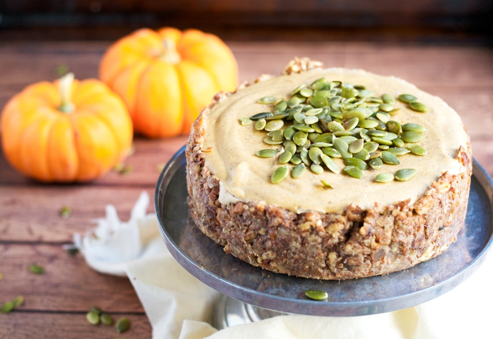 A small vegan pumpkin cheesecake topped with pumpkin seeds on a cake stand in front of two mini pumpkins.