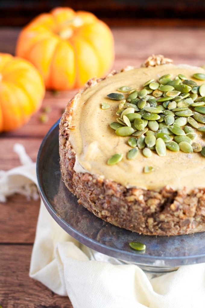 A small vegan pumpkin cheesecake with nut crust and topped with pumpkin seeds on a cake stand with mini pumpkins in the background.
