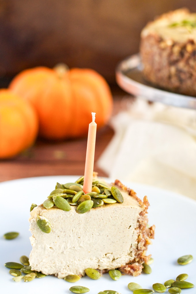 A slice of vegan pumpkin cheesecake topped with pumpkin seeds and an orange candle.