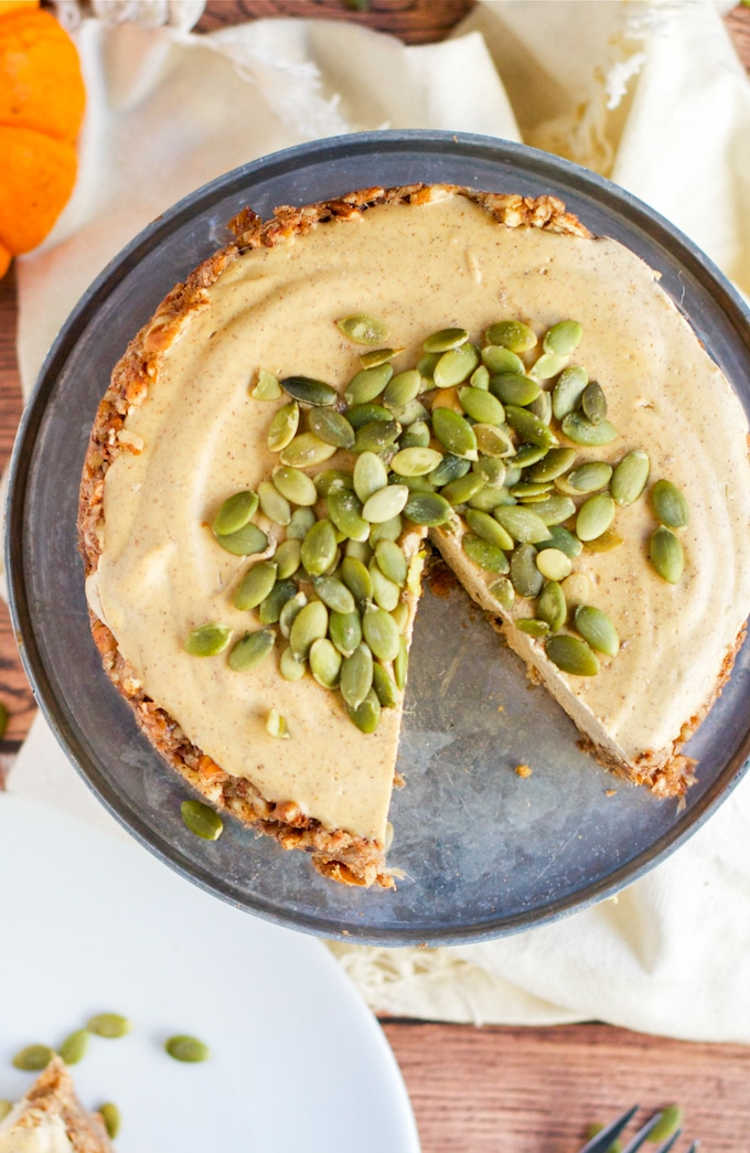 An overhead view of a vegan pumpkin cheesecake topped with pumpkin seeds with one slice removed.