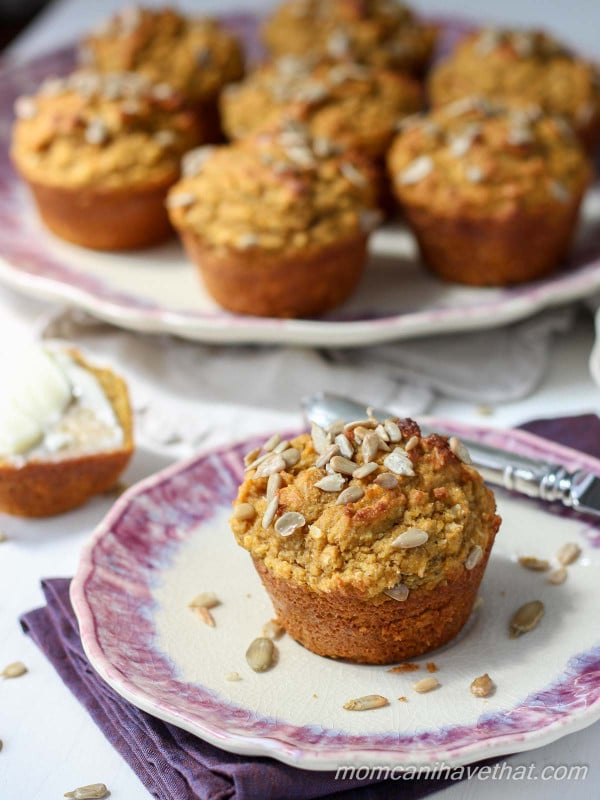 A pumpkin muffin on a plate with a platter of muffins behind it.