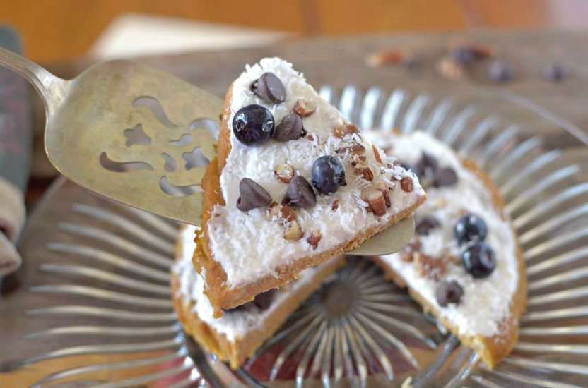 pumpkin breakfast pizza topped with coconut, blueberries, pecans and chocolate chips.