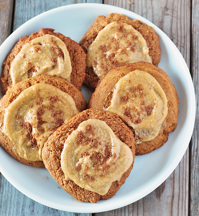 A plate of pumpkin cookies topped with maple glaze and ground cinnamon.