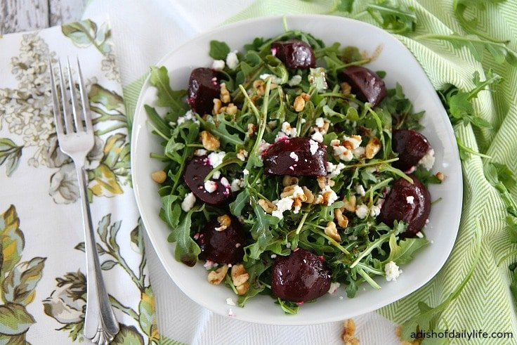 A bowl of arugula salad with roasted beets, walnuts and goat cheese.