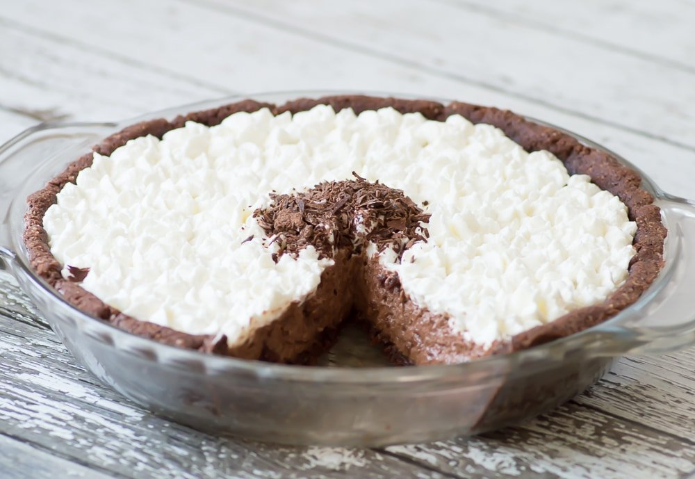 A french silk pie with whipped cream on top with a wedge taken out of it.