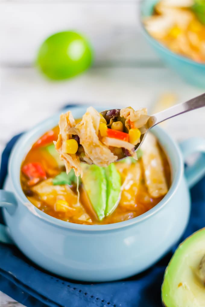 A spoon full of chicken tortilla soup over a bowl of soup.