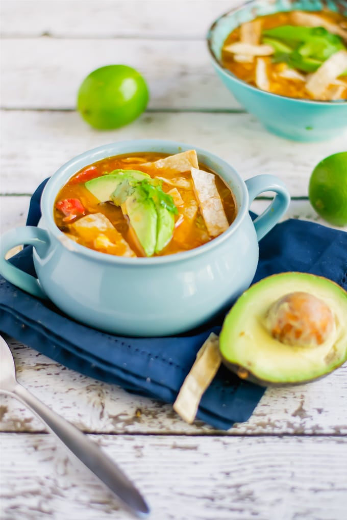 A crock of chicken tortilla soup topped with avocado and cilantro.