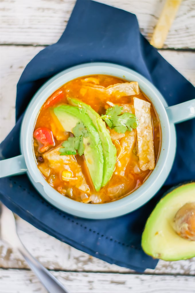 A bowl of chicken tortilla soup topped with avocado slices and cilantro.