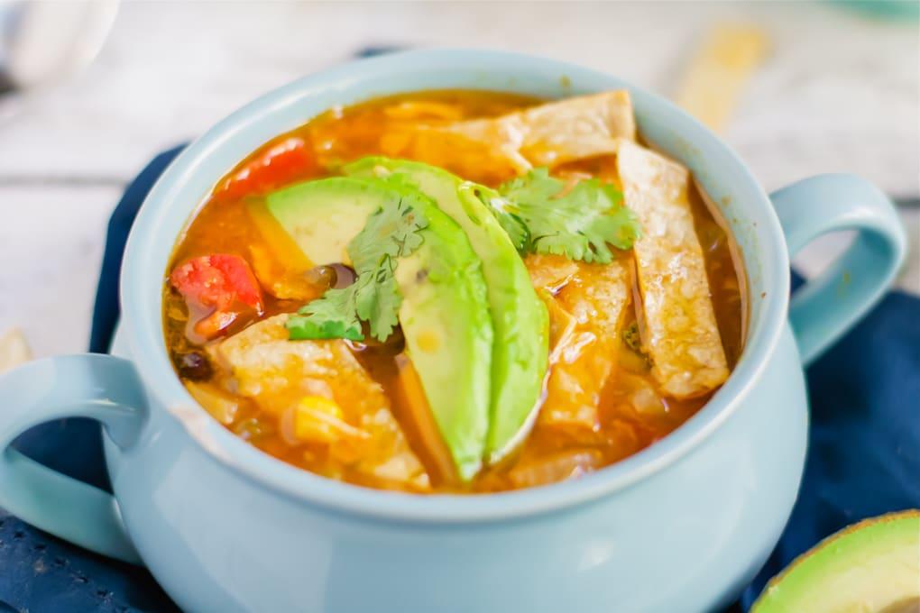A blue soup bowl of chicken tortilla soup topped with tortilla strips, avocado slices and cilantro.