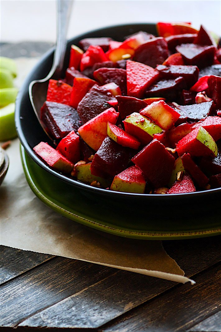 A bowl of Marinated Beet and Apple Salad with a spoon in it.