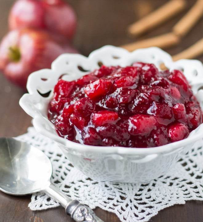 A bowl of apple cranberry sauce with a spoon in the foreground.