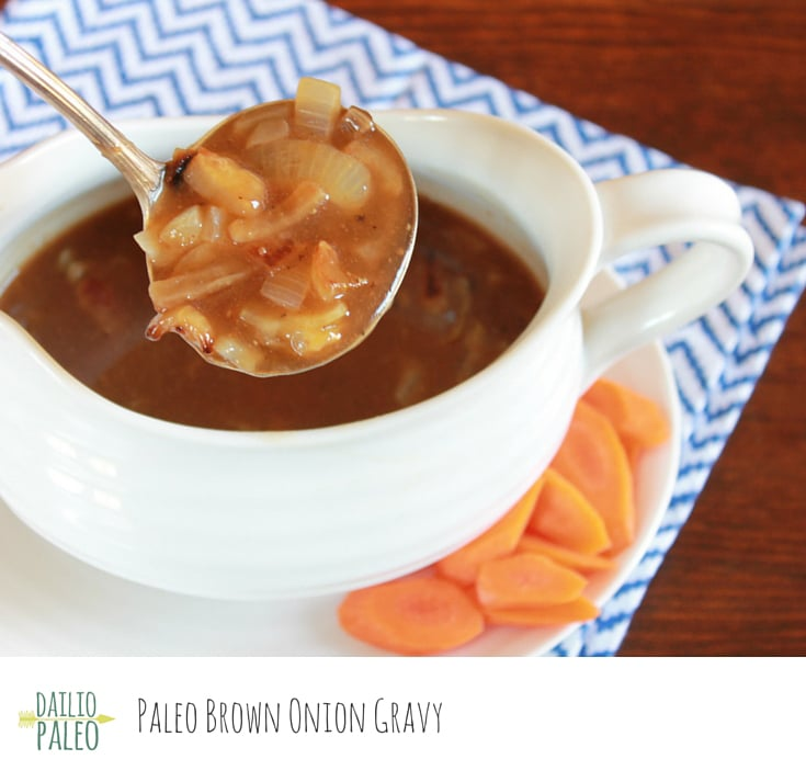A gravy boat of brown onion gravy with a spoon in it and carrots on the side.