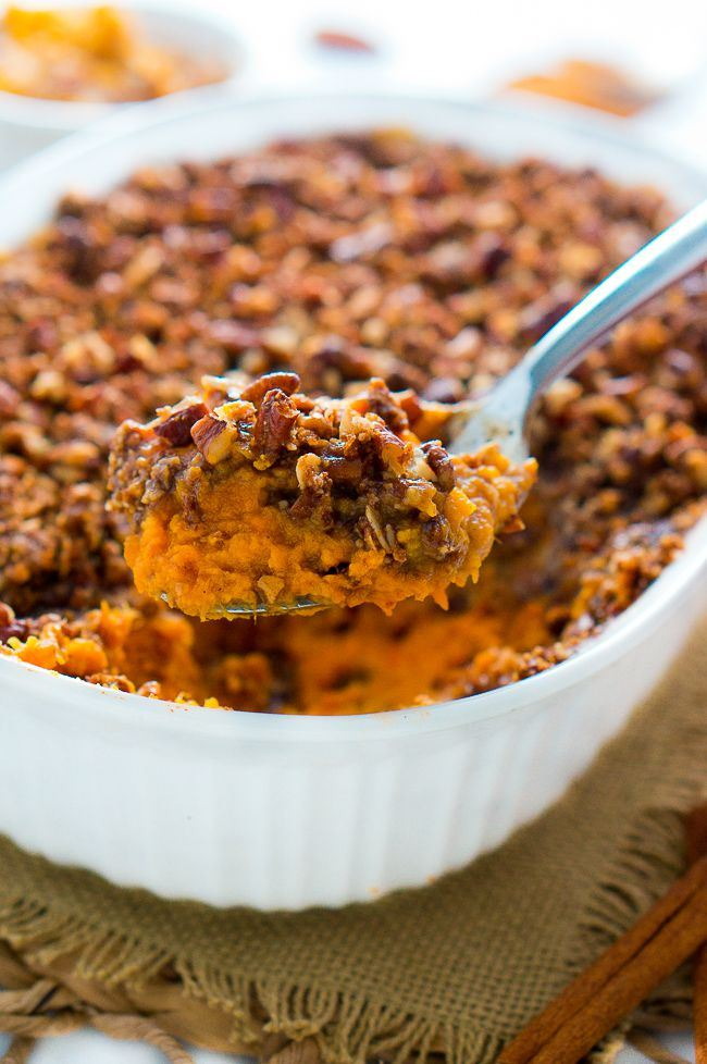 A casserole dish of mashed sweet potatoes topped with nuts.